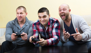 Three positive adult guys sitting on sofa with joysticks indoors