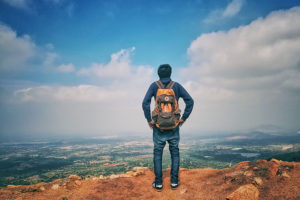 man in backpack thinking about addiction recovery programs
