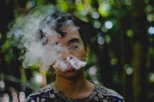 Man with cloud of cigarette smoke wondering if he is addicted to something.