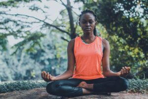 Woman in yoga clothes meditating to battle addiction in park.