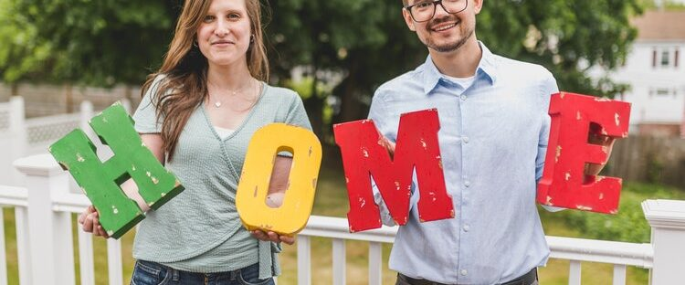 Man and woman holding up home blocks for sober living house